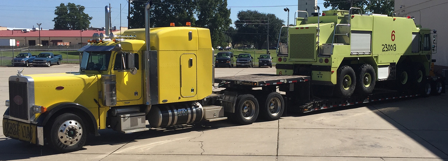 Yellow truck carrier transporting heavy machinery
